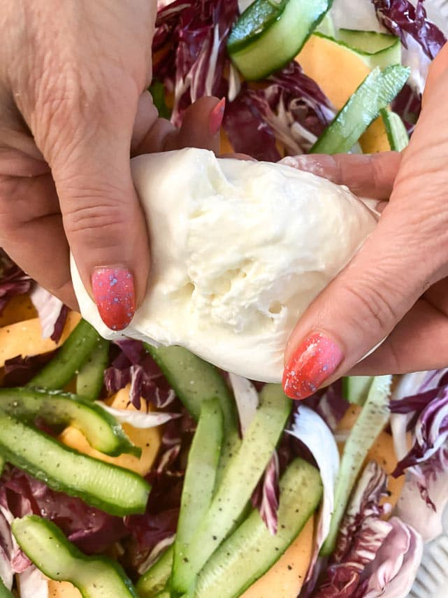 breaking open burrata by hand over a salad
