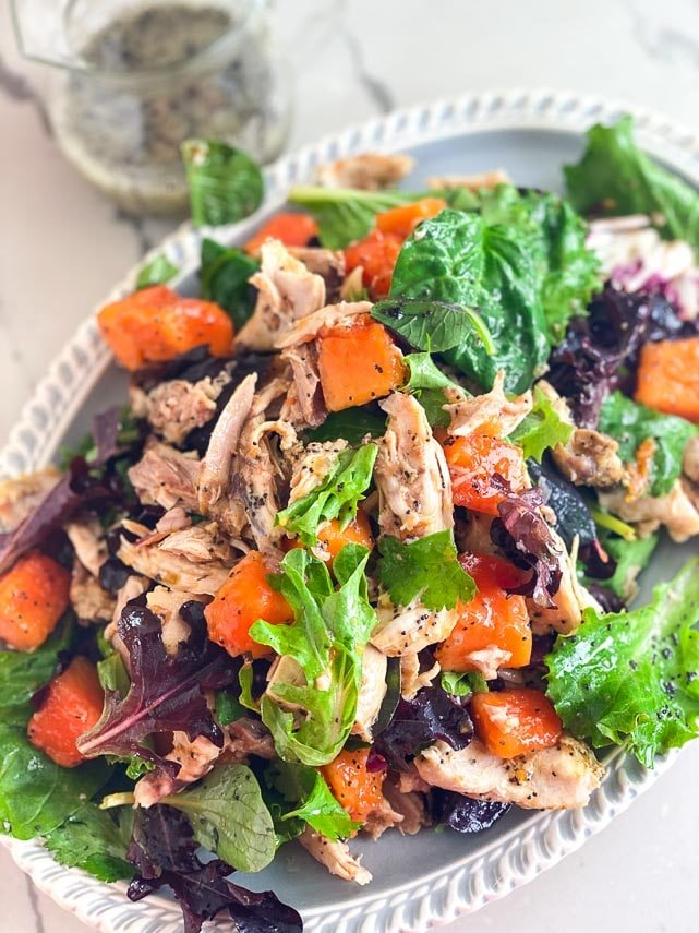 closeup image of Low FODMAP Chicken Papaya Salad with Poppy Seed Dressing on oval platter with dressing background