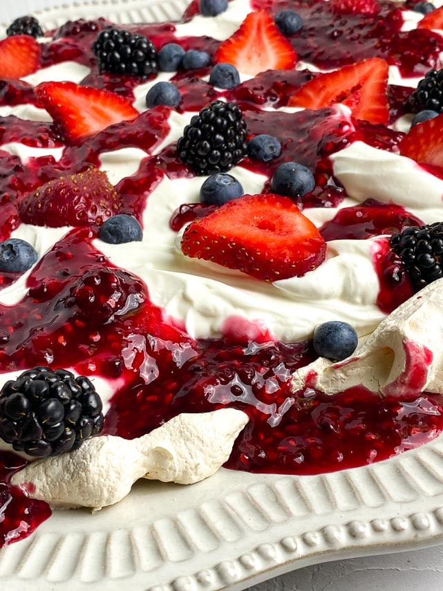 closeup of Low FODMAP Mixed Berry Slab Pavlova showing fruit, cream and sauce