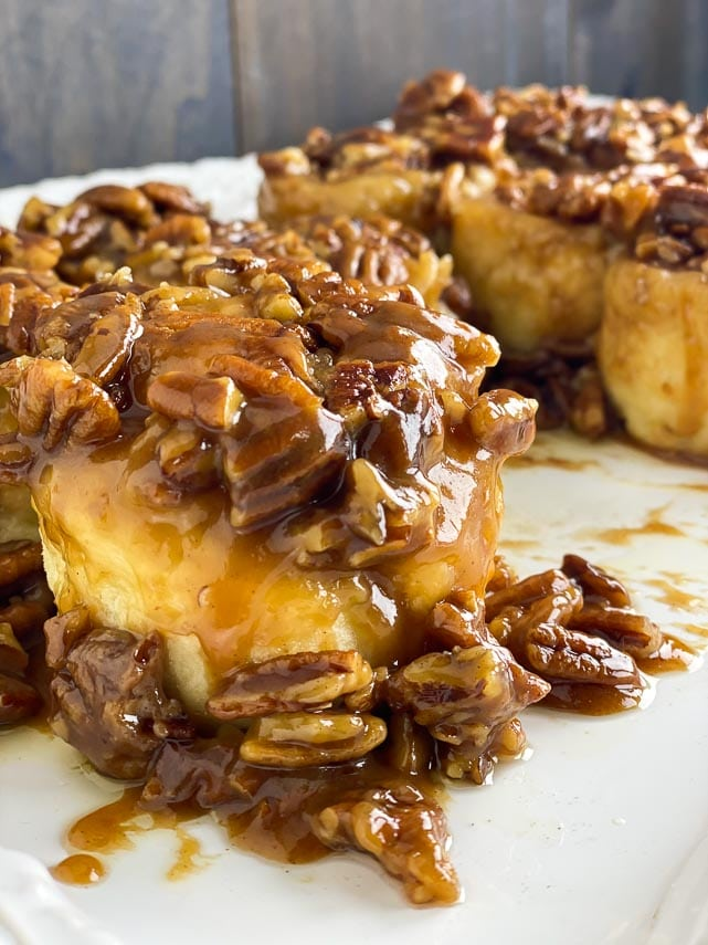 closeup of low FODMAP gluten-free caramel pecan sticky buns on white plate, nuts spilling down side