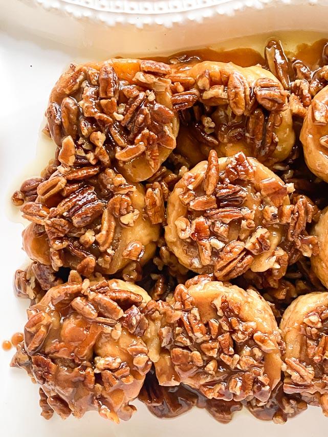 closeup of low FODMAP gluten-free caramel pecan sticky buns on white platter