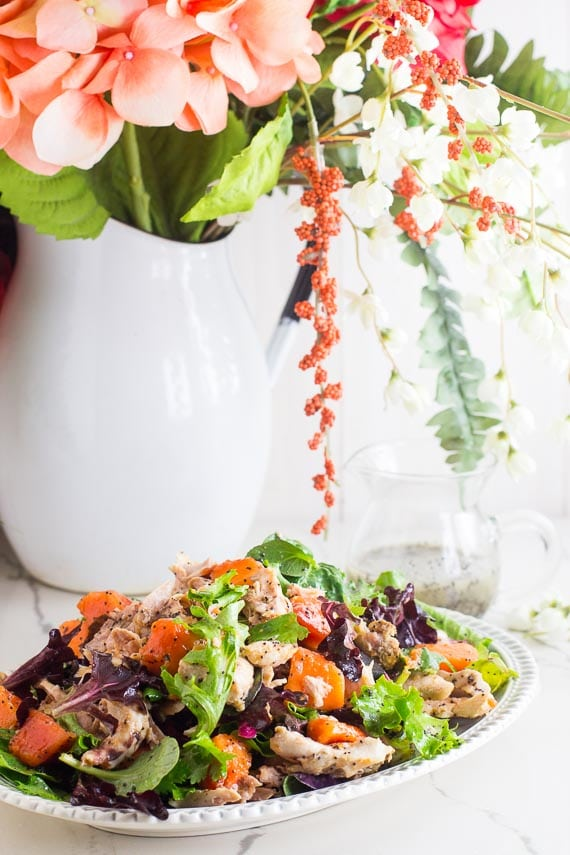 colorful vertical image of chicken papaya salad on oval platter with flowers in white vase in background