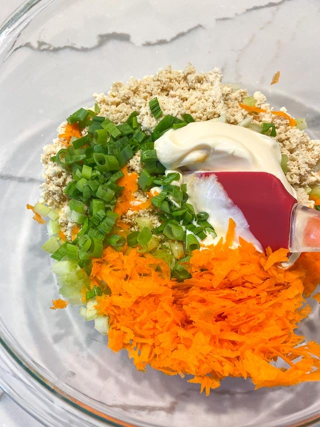 combining ingredients for tofu salad in glass bowl