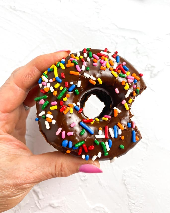 holding a cocoa glazed chocolate doughnut with multi-colored sprinkles