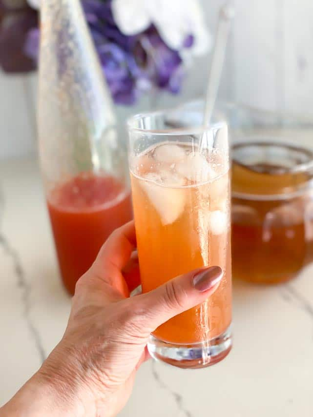 holding a glass of peach iced tea
