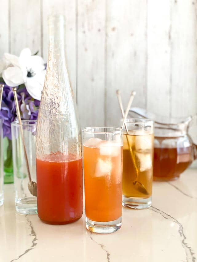 ice tea with and without peach puree added, in tall glasses with silver spoons