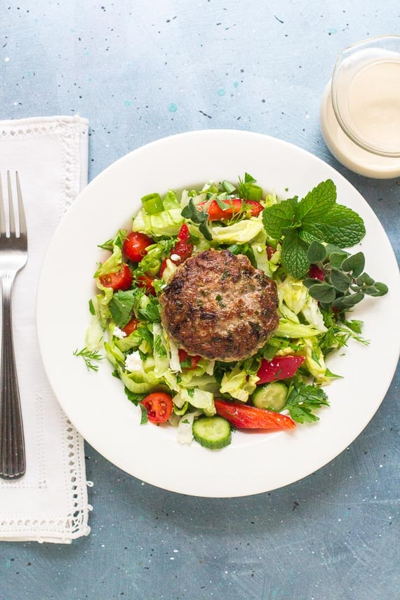 low FODMAP Burger with Tahini Sauce before it is drizzled with sauce on white plate