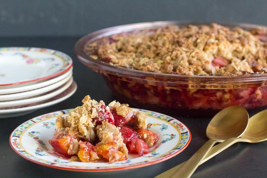low FODMAP strawberry peach crisp on a decorative plate and in pie plate in background; gold colored spoons