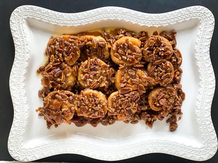overhead low FODMAP gluten-free caramel pecan sticky buns on decorative white platter