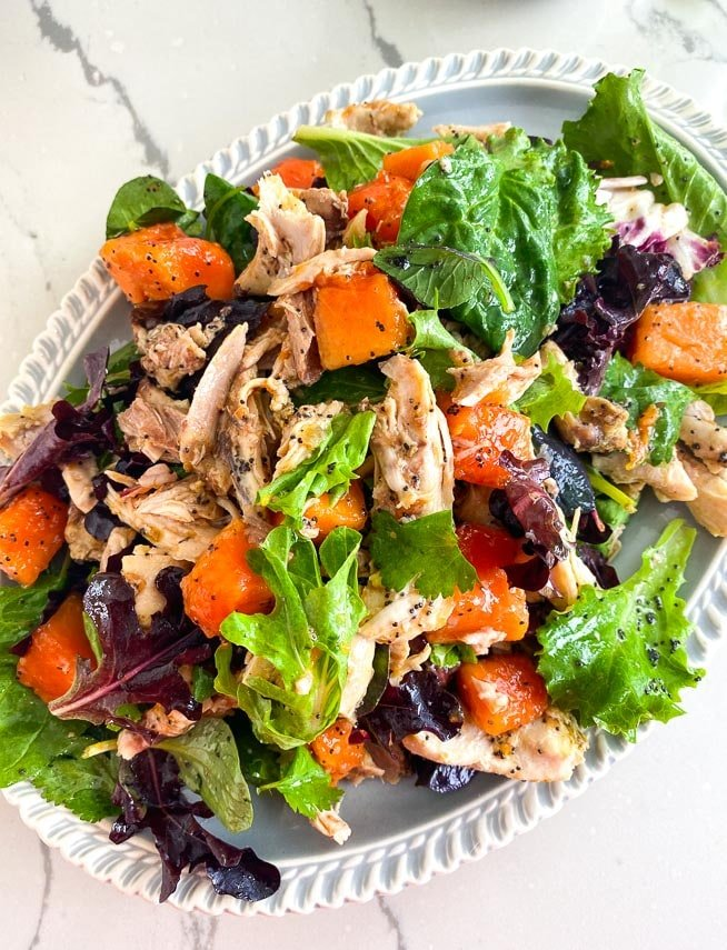 overhead image of Low FODMAP Chicken Papaya Salad with Poppy Seed Dressing on oval platter
