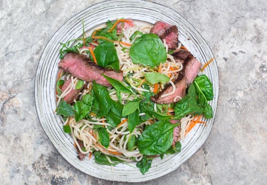 overhead image of Low FODMAP Thai Basil Steak Salad on rustic round white plate