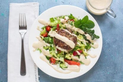 overhead shot of low FODMAP Lamb Burgers with Tahini Sauce on salad and white plate; linen napkin and fork alongside