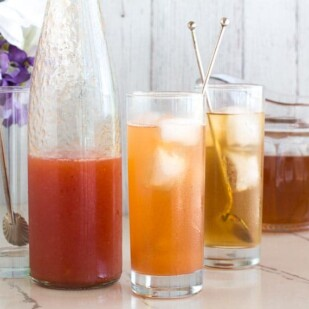 peach iced tea in tall glasses with silver spoons against white backdrop_