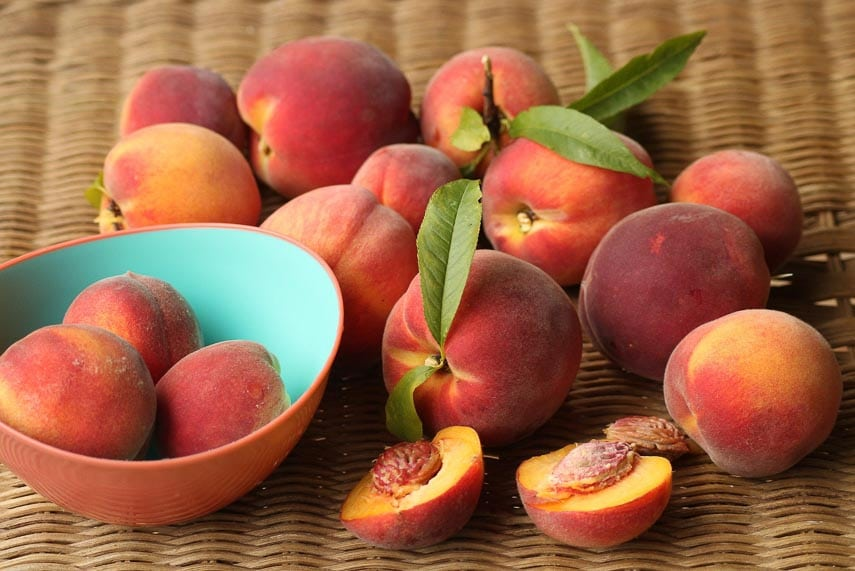 peaches on a wooden surface; some cut open