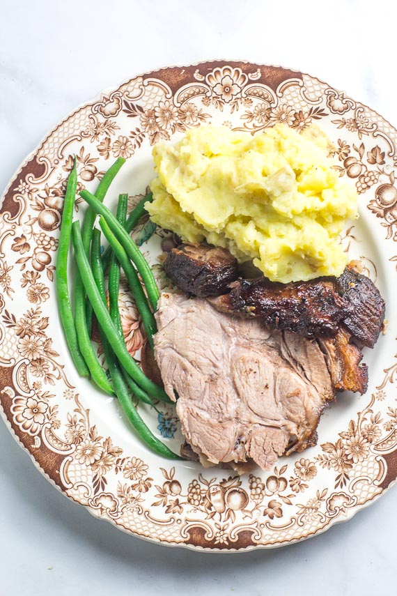 plate of Low FODMAP Porchetta Pork Roast, sliced, with green beans on a brown and white plate, with mashed potatoes
