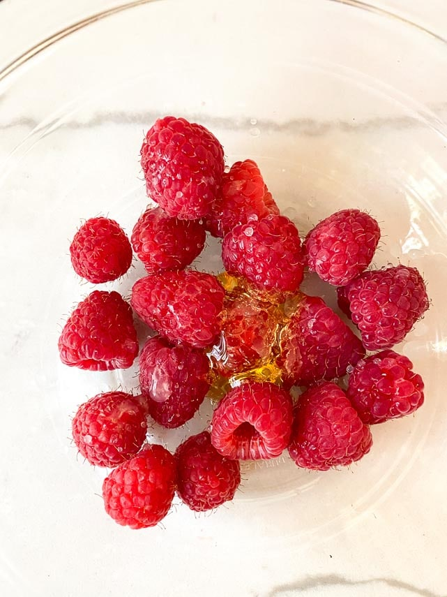 raspberries and honey in glass bowl