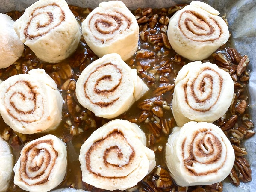 raw sticky buns on top of sticky sauce in pan ready to bake