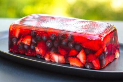 side view of Low FODMAP Mixed Berry Terrine on an oval black plate; outside on deck - garden in background