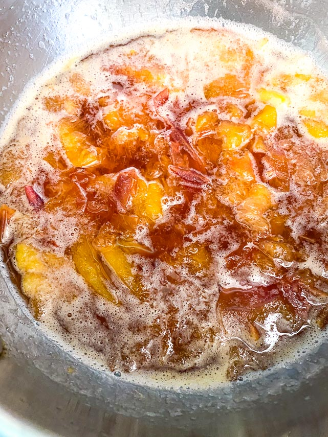 simmering peaches, sugar and water in a pot