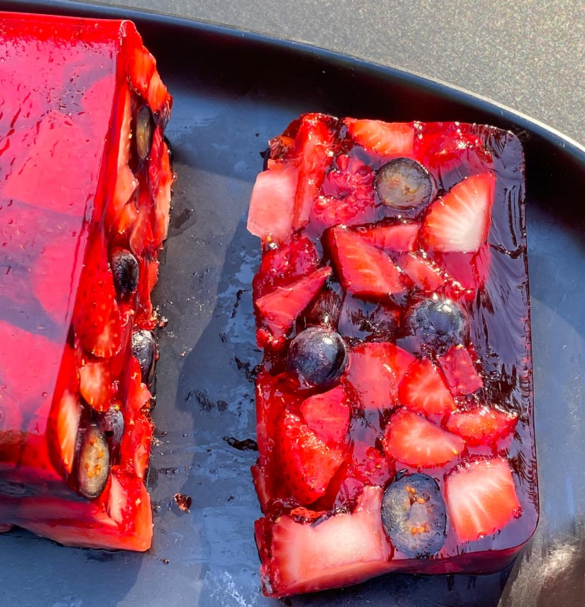slice of Low FODMAP Mixed Berry Terrine on an oval black plate; outside on deck in sunlight