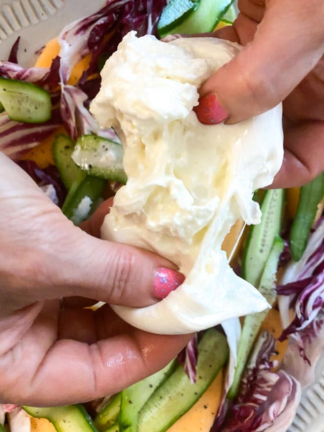 tearing burrata into bite-sized pieces