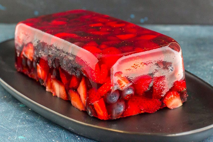 three-quarters view of Low FODMAP Mixed Berry Terrine on an oval black plate; blue background