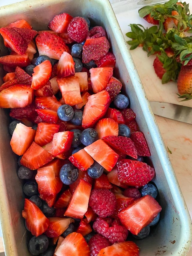 tossing cut fruit together in metal loaf pan for terrine
