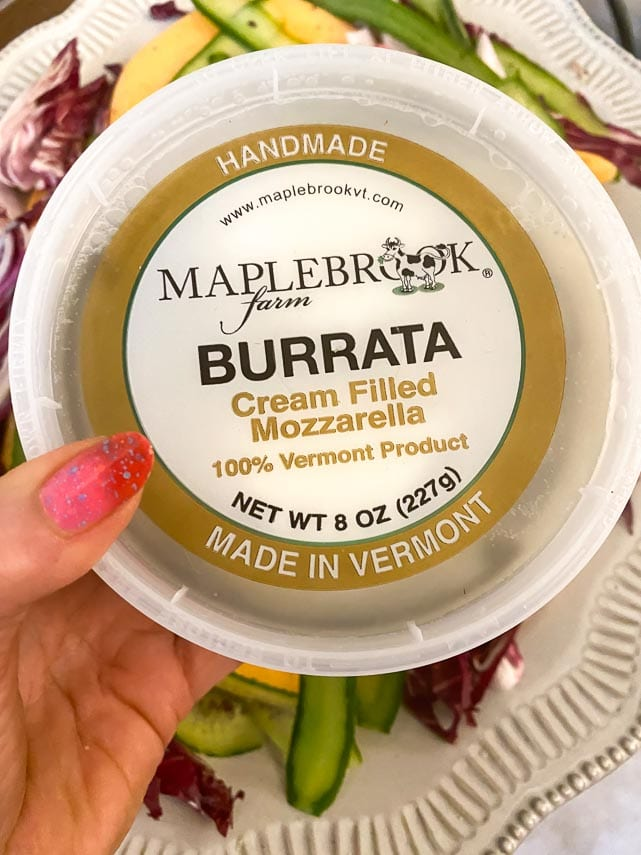 tub of burrata held in hand