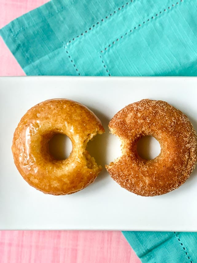 two low FODMAP Baked Doughnuts on rectangular white plate; one glazed; one with cinnamon sugar