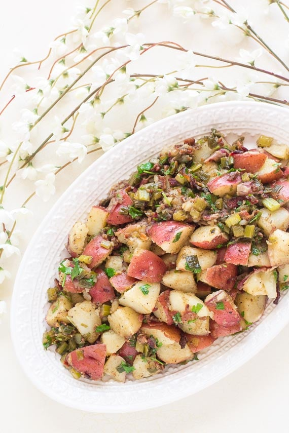 vertical image of Low FODMAP Hot Potato Salad with bacon on decorative oval white platter