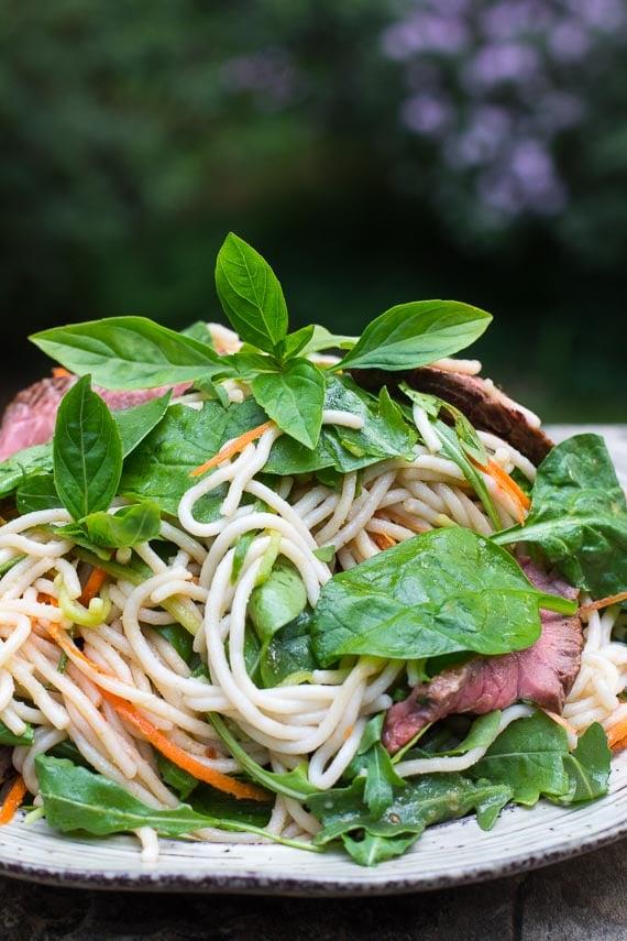 horizontal image of Low FODMAP Thai Basil Steak Salad on rustic round white plate