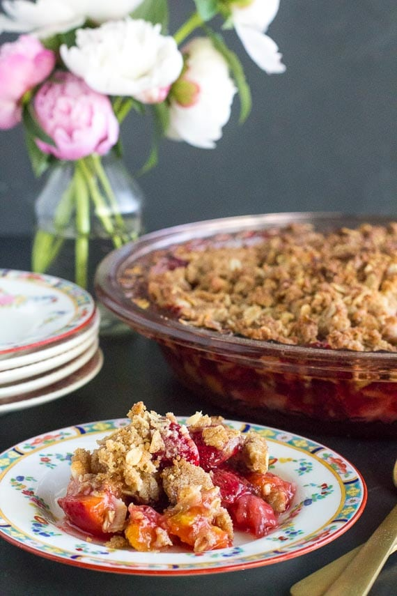 vertical image of low FODMAP strawberry peach crisp on a decorative plate and in pie plate in background
