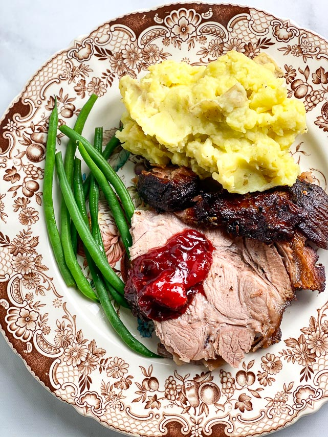 Brown and white plate holding low FODMAP Porchetta Pork Roast with mashed potatoes, green beans and Blackberry Peach Chutney