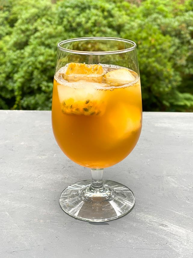 Clear footed glass of green iced tea with passionfruit ice cubes