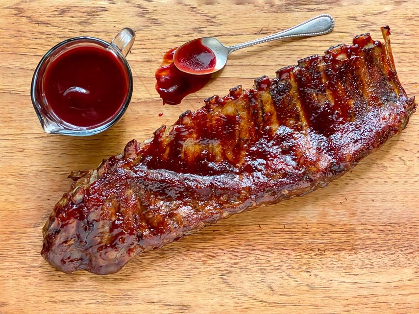 Low FODMAP Blackberry Maple BBQ Rib rack on wooden board with extra sauce