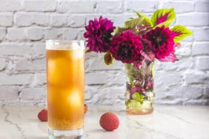 Low FODMAP Iced Black tea with Lychees in tall clear glass; white background and magenta flowers in a small vase