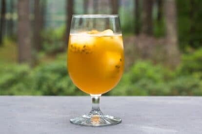 Low FODMAP Iced Green tea with Passionfruit in a clear footed glass on gray surface; outdoors