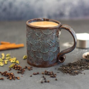 Low FODMAP Masala Chai in a decorative mug on dark surface surrounded by spices, tea and sugar