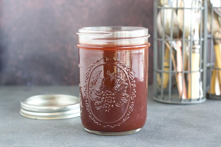 Low FODMAP sweet and sticky BBQ sauce in open mason jar, lid on the side; dark counter