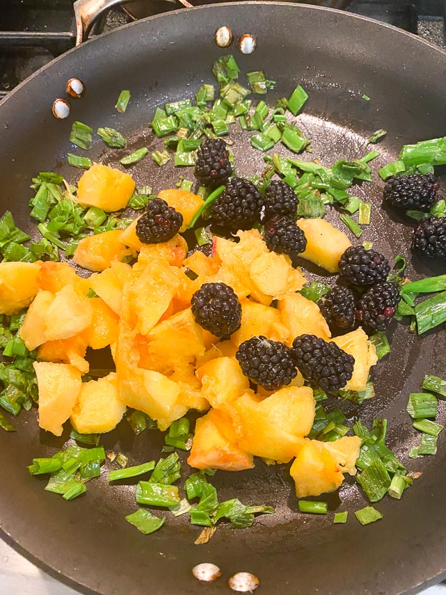adding blackberries and peaches to pan for chutney