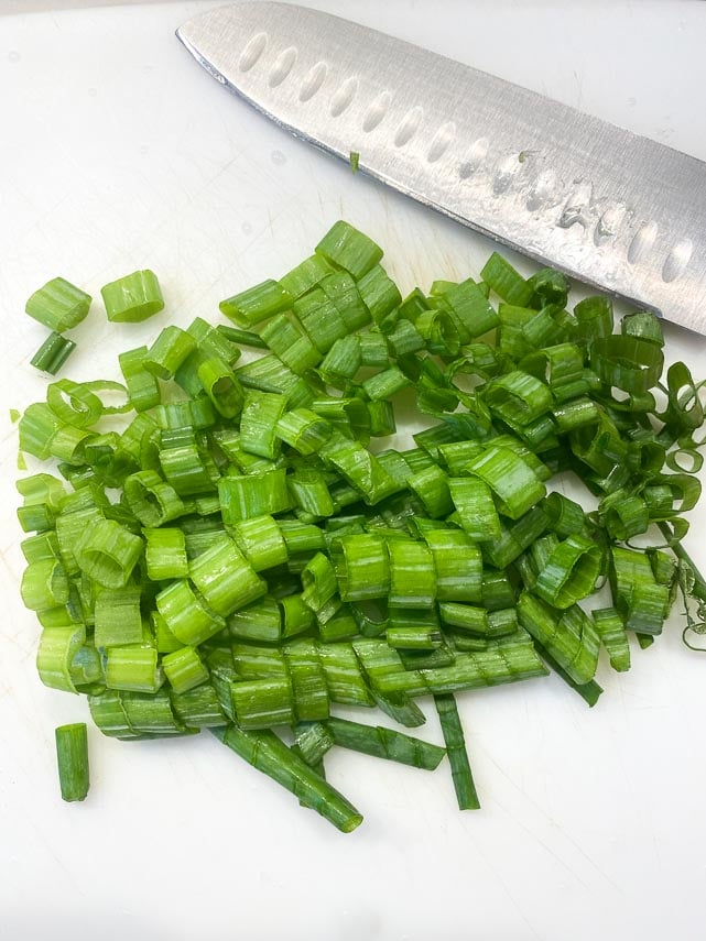 chopped scallion greens on cutting board with knife
