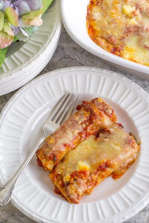 closeup image of Low FODMAP Manicotti on a white plate with silver fork; green napkin