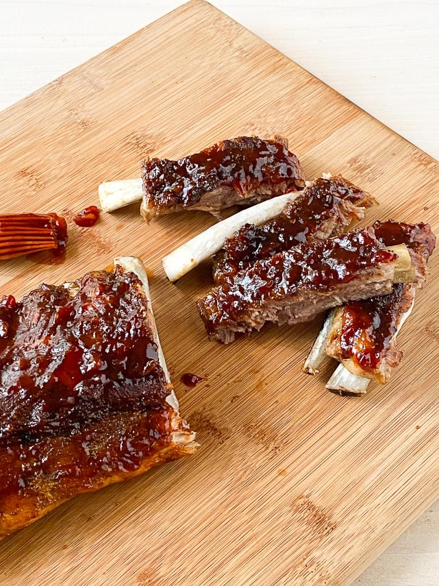 closeup of Low FODMAP Pineapple Whiskey BBQ ribs, cut and separated from rack, on wooden board