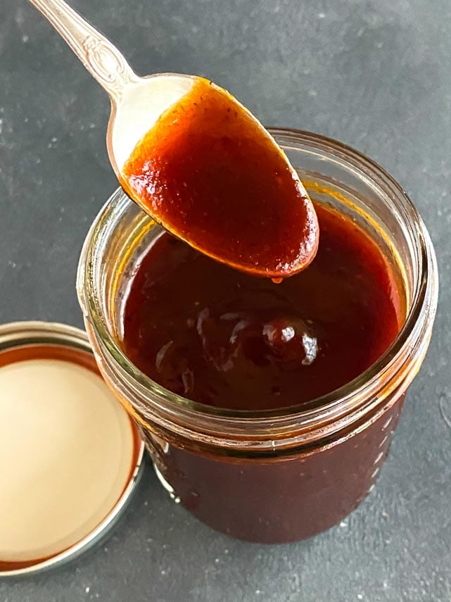 closeup of sweet and sticky BBQ sauce on a spoon, dripping into a jar against dark background