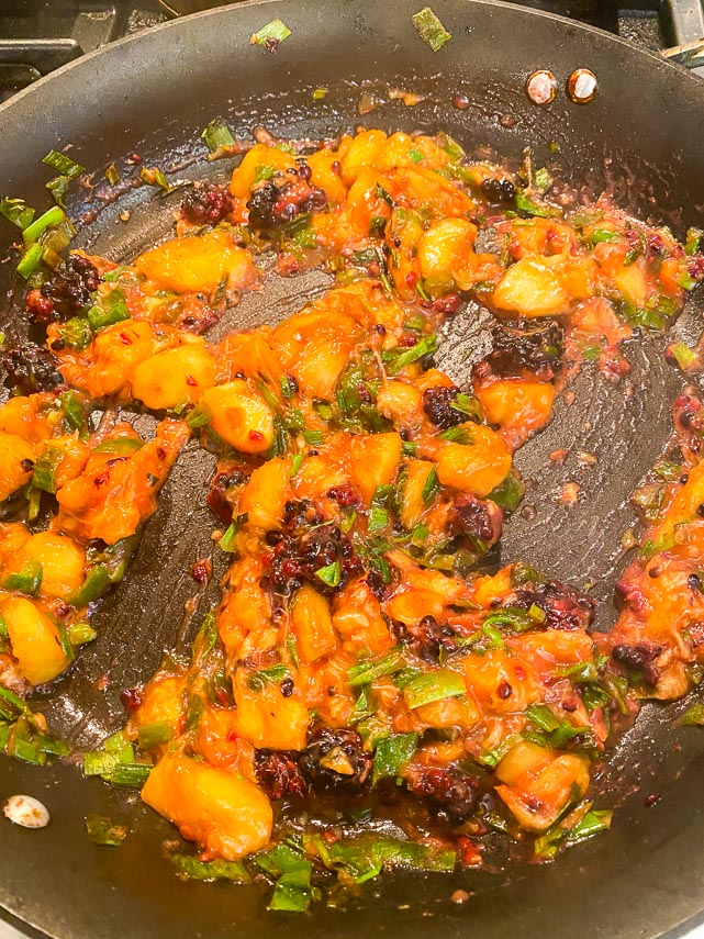 cooking blackberries and peaches until juicy for chutney