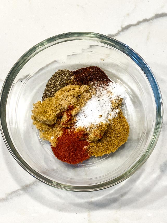 dry rub for ribs in clear glass bowl on white marble counter