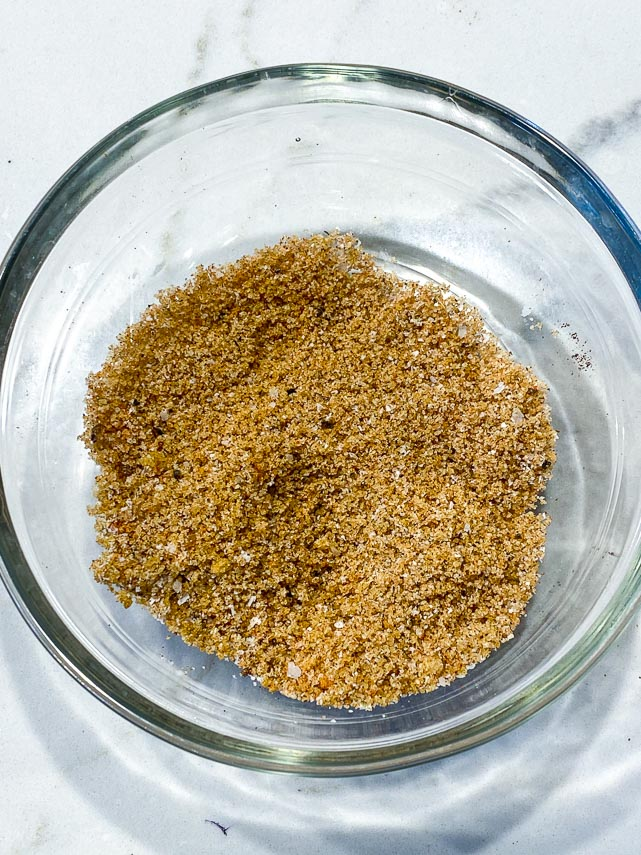 dry rub for ribs in clear glass bowl , stirred together, on white marble counter