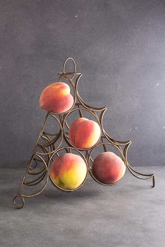 fruit ripening rack on dark background, holding 4 peaches