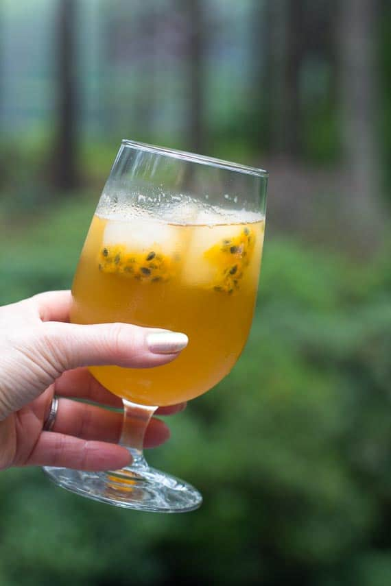 glass of low FODMAP iced green tea with passionfruit ice cubes in goblet; held in hand