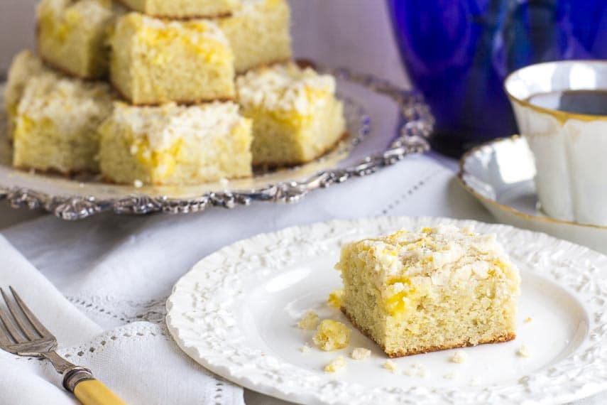horizontal image of Low FODMAP Lemon Crumb Cake on a silver platter and on white plate; coffee cup in background